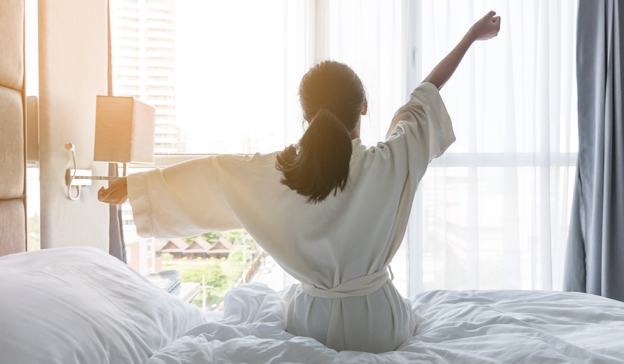 Woman stretching in the morning on the side of her bed.